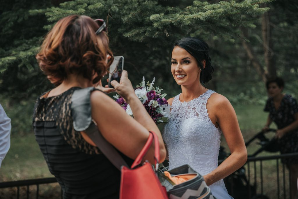 guest takes photo of beautiful bride with cell phone