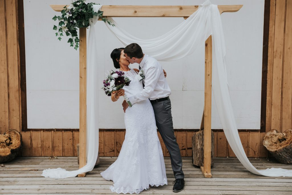 groom dips bride for kiss under ceremony arch