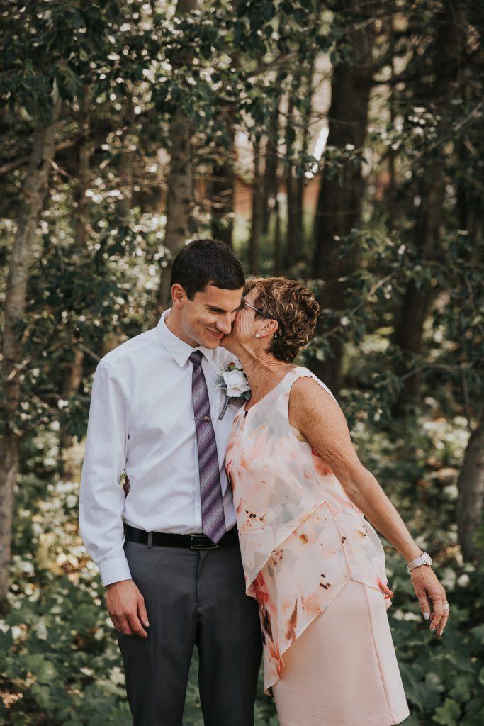 grooms mom kisses him on the cheek family wedding photos