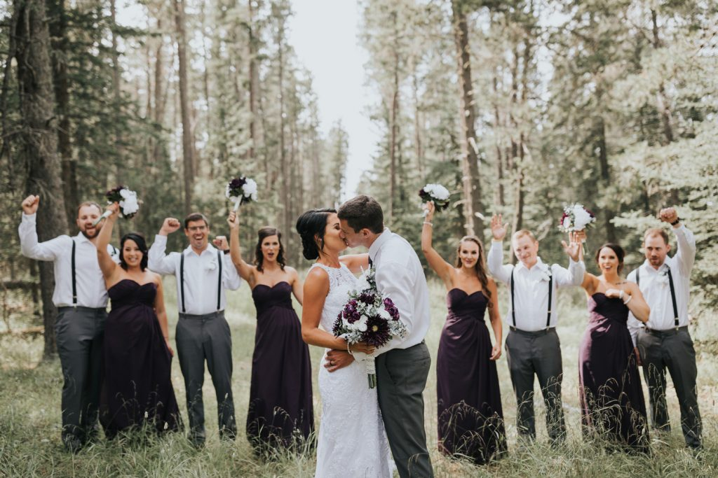 bride and groom kiss with bridal party cheering behind