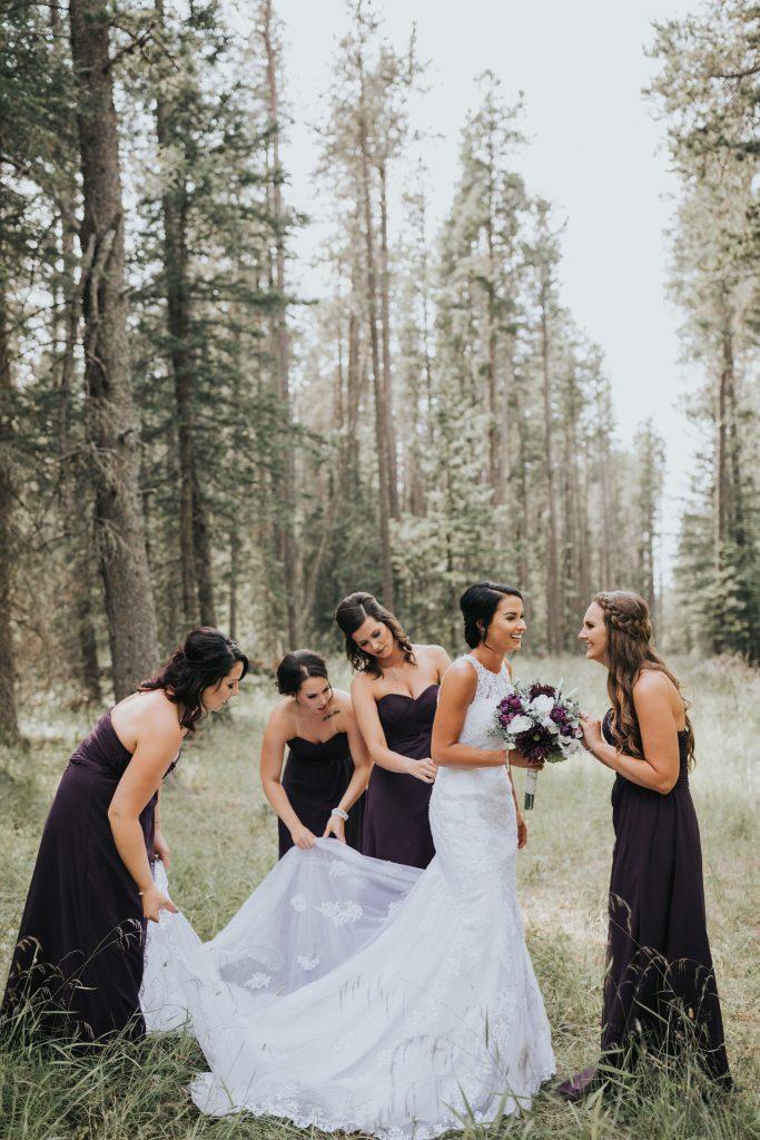 bridesmaids help fix bride's long train wedding dress