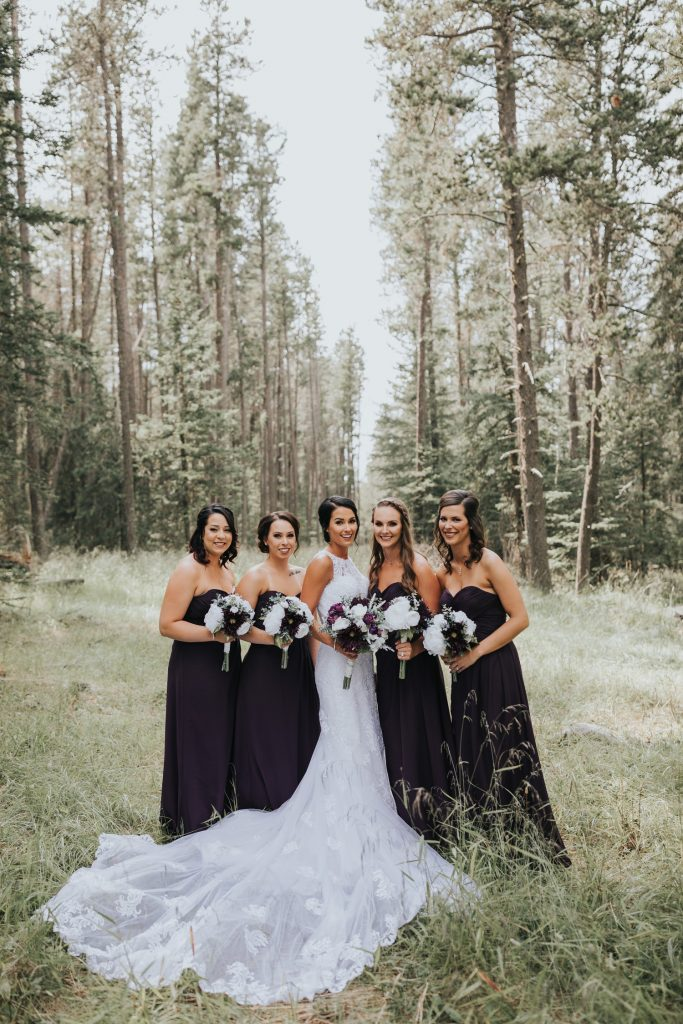 bridesmaids pose with bride long train in front