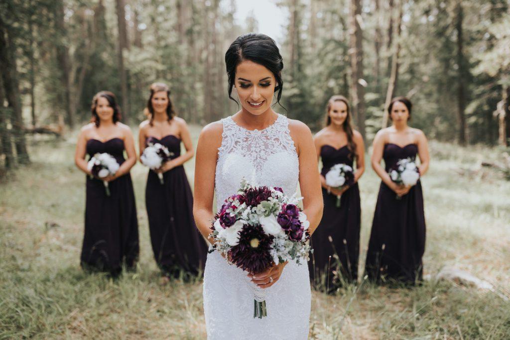 bride posing with bridesmaids behind her