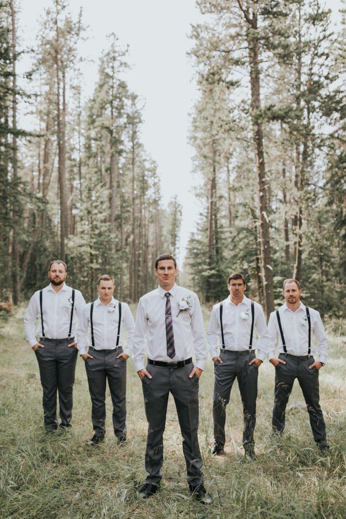 groom posing with groomsmen behind him