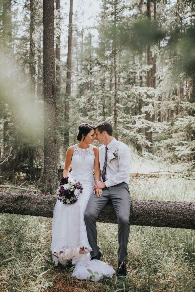 bride and groom sitting close on tree log