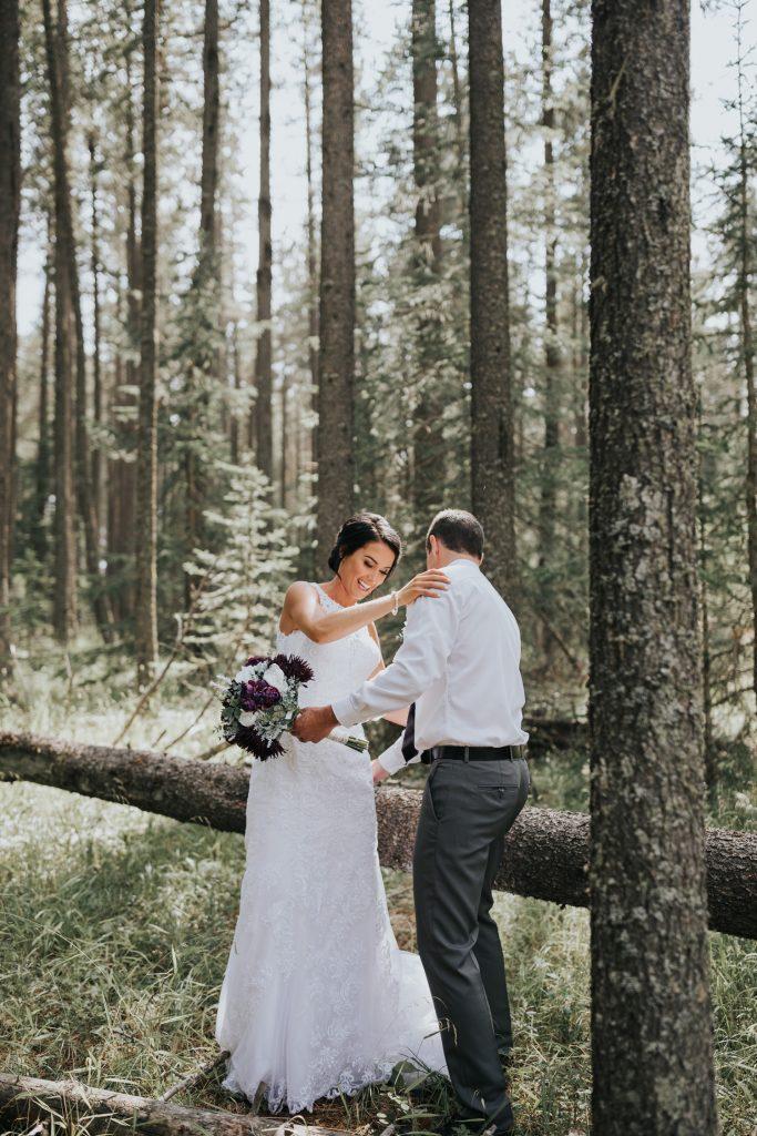 groom helps bride off tree log
