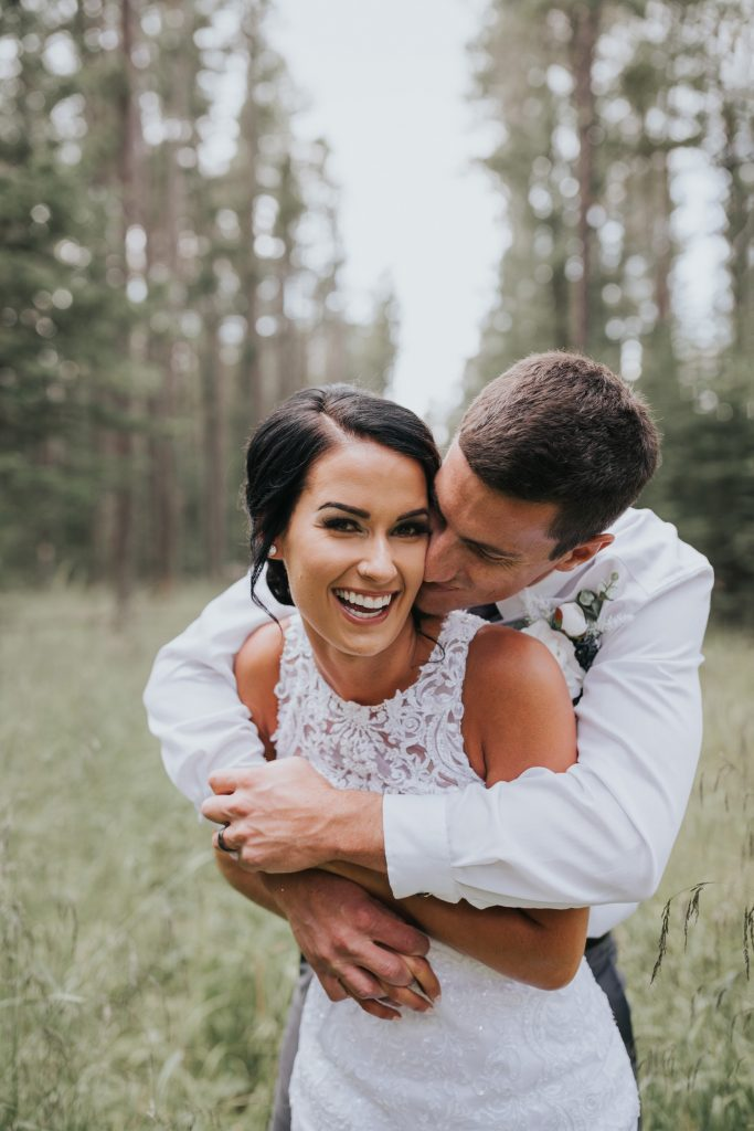 bride laughs as groom kisses her cheek