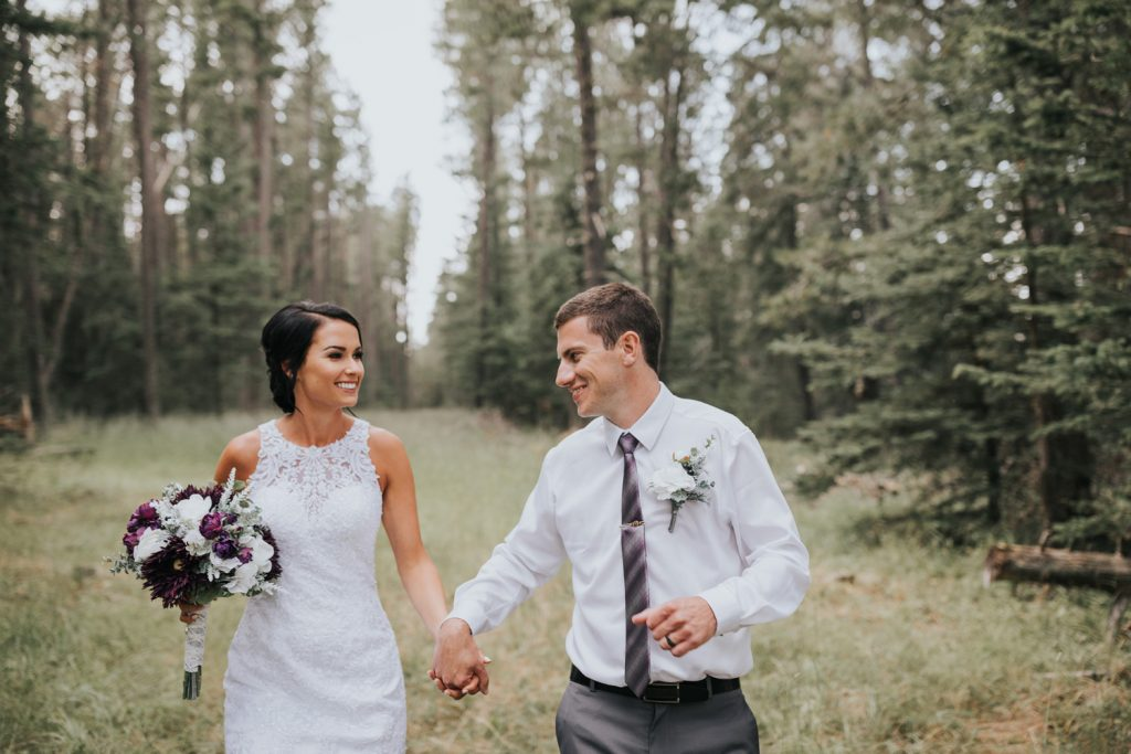 bride and groom holding hands running