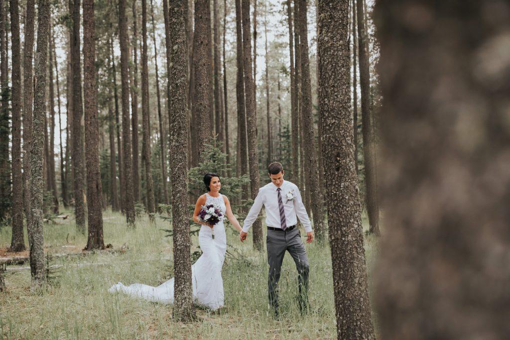 wedding couple walking in elkwater woods