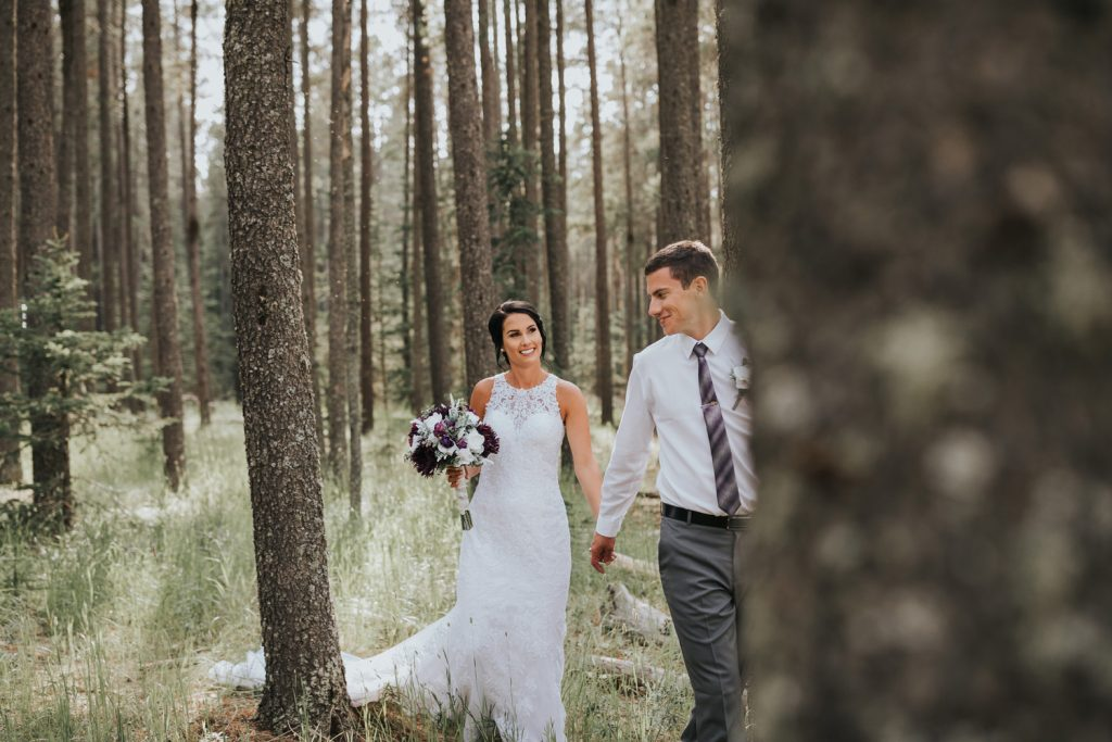 bride smiles as groom leads her through trees cypress hills alberta