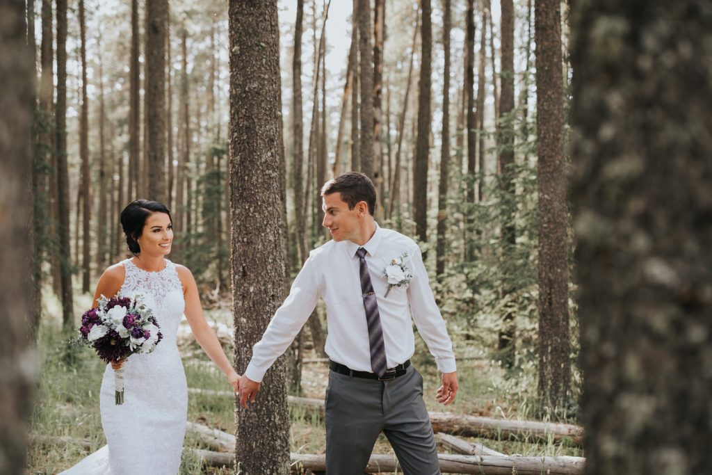 groom leading bride into forest elkwater