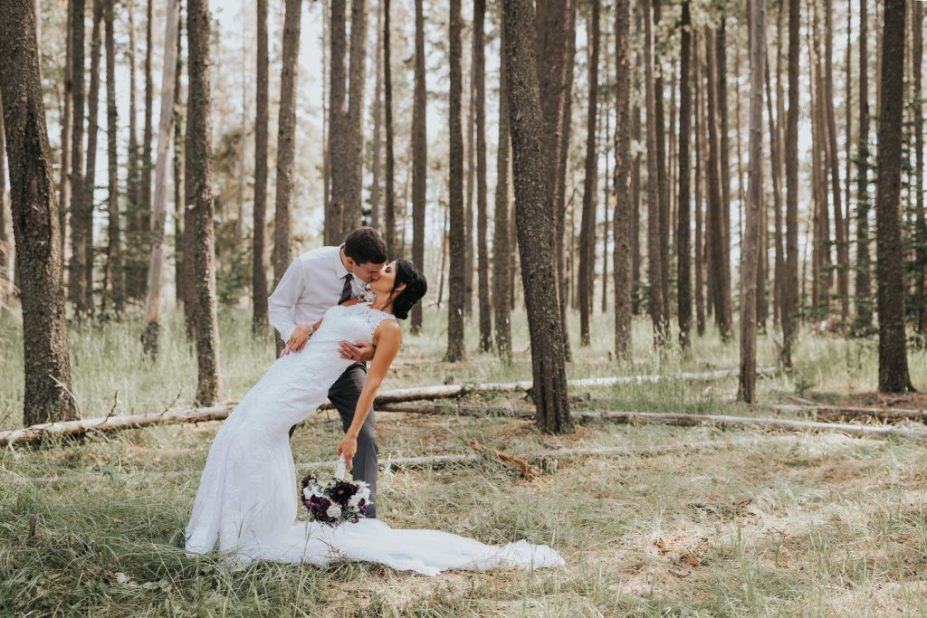 groom dipping bride for a kiss elkwater forest