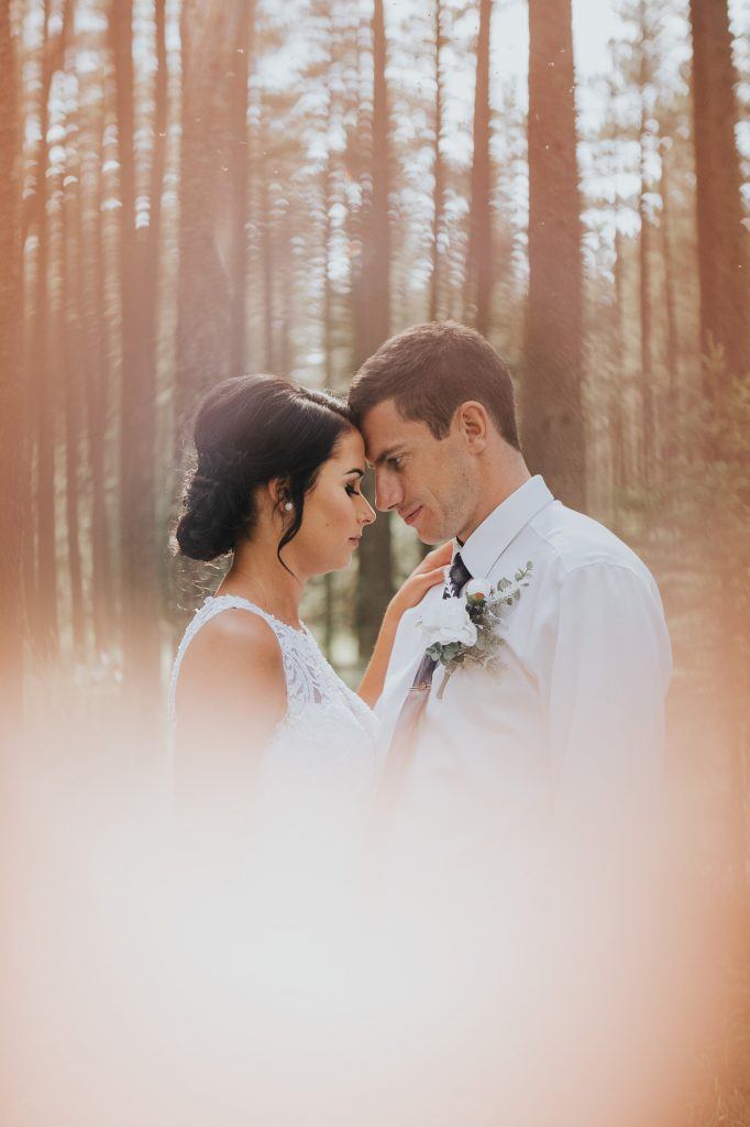 bride and groom standing foreheads touching ring of fire