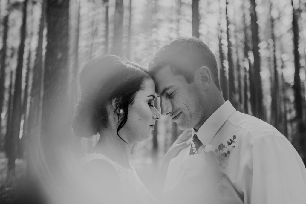 bride and groom foreheads touching eyes closed wedding ring of fire