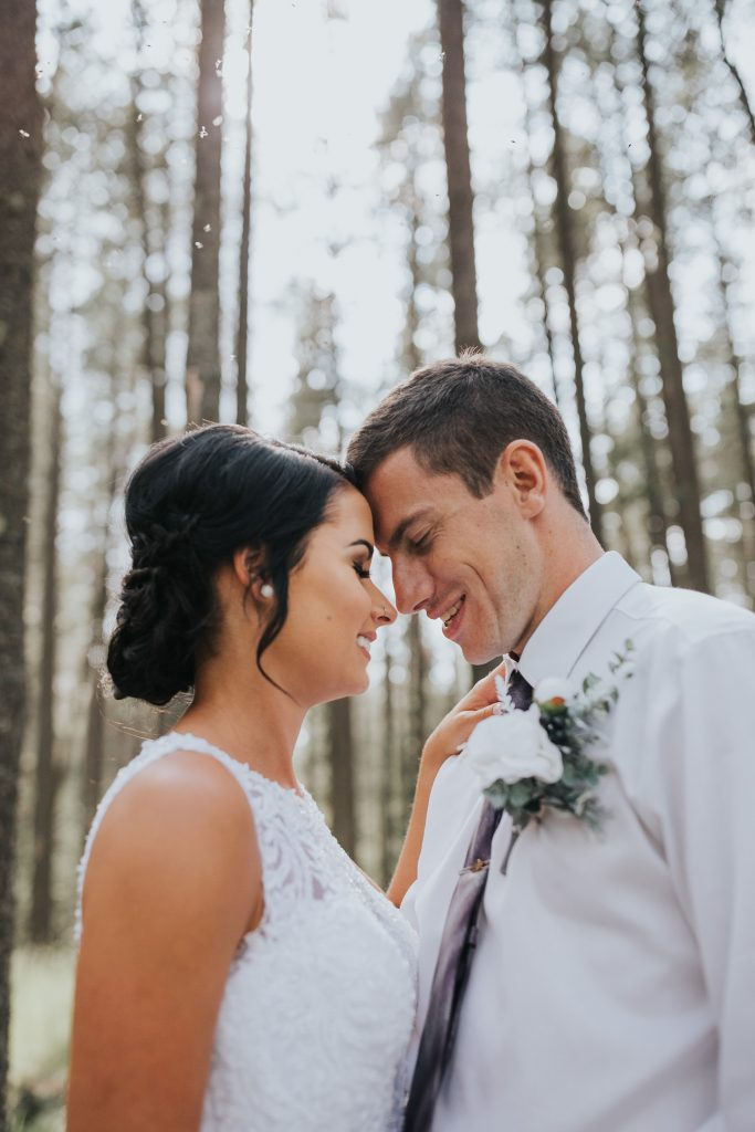 bride and groom smile foreheads together in sunlight