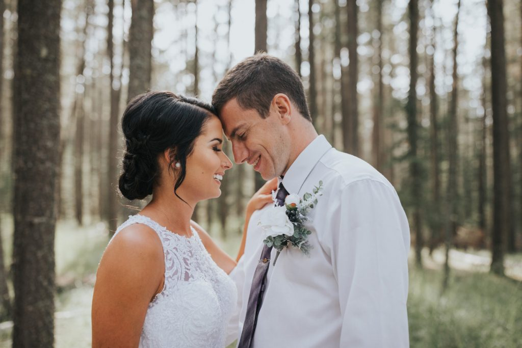 bride and groom laugh standing close in forest