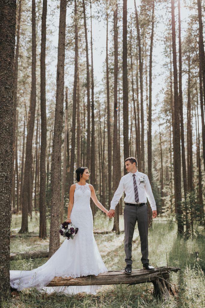 bride and groom hold hands standing on tree log