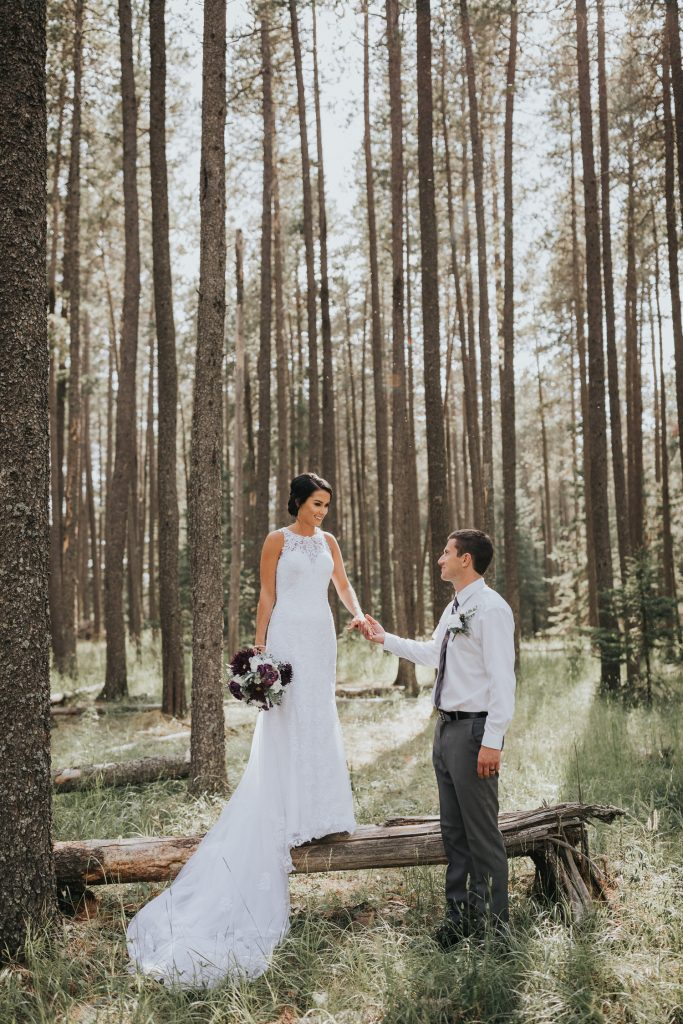 bride standing on tree log holding grooms hand
