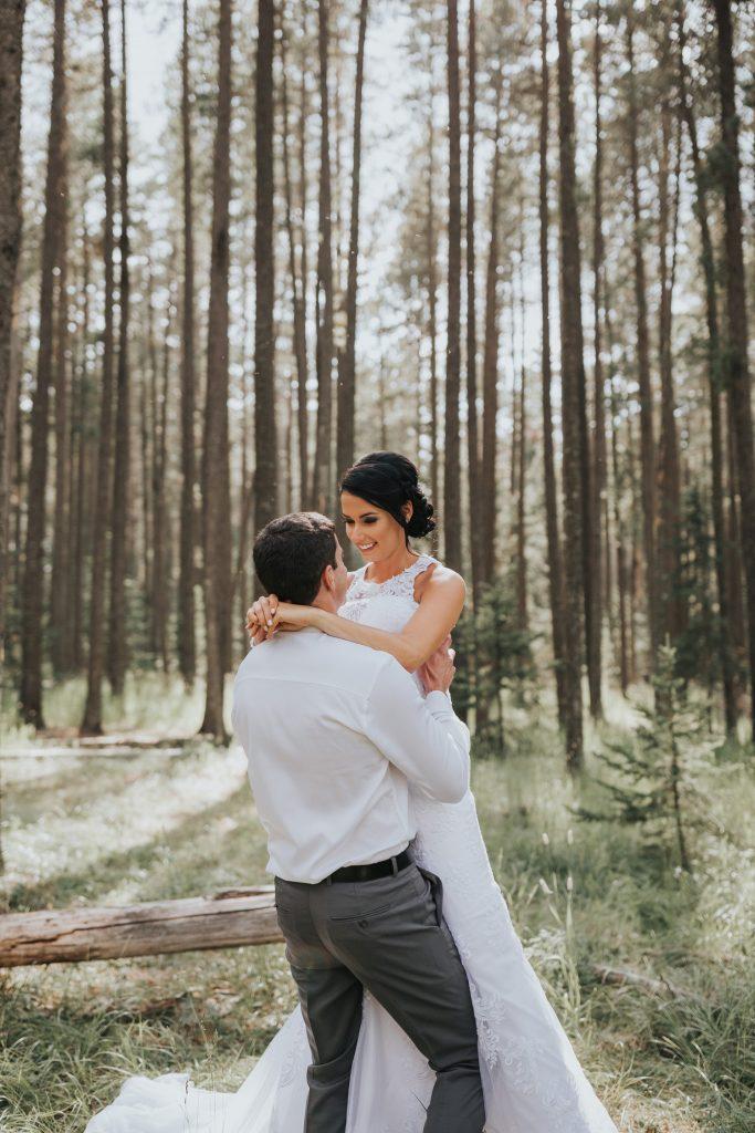 groom carries bride off tree log