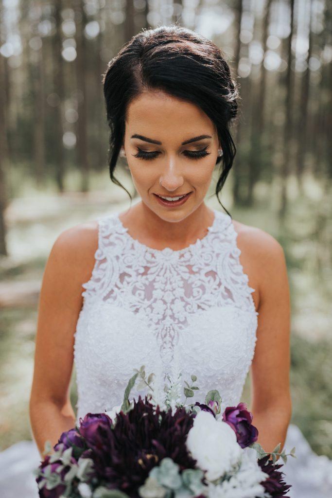 portrait of bride looking down at wedding bouquet