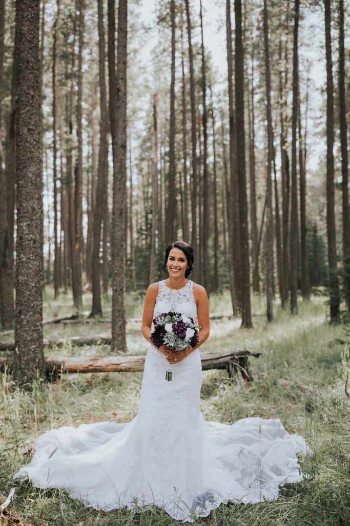 portrait of bride standing in elkwater forest big dress train