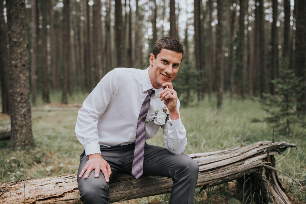 portrait of groom sitting on tree log elkwater forest