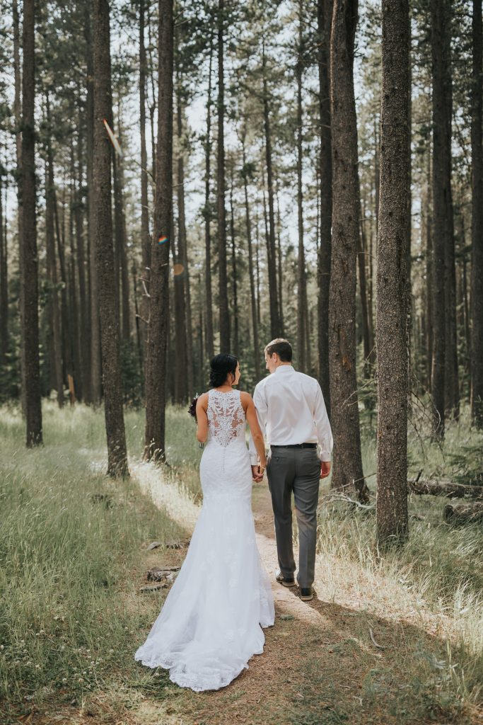 bride and groom walking into elkwater forest sunlight
