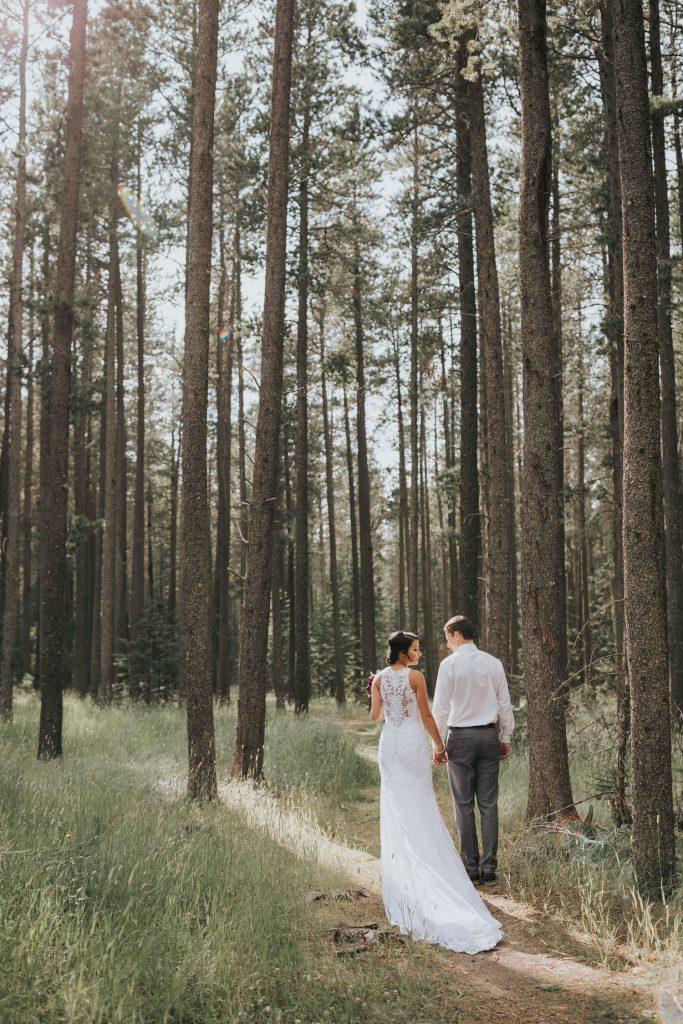 wedding couple walks into elkwater forest sunlight