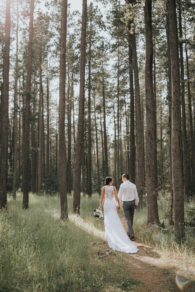 bride and groom hold hands walk into trees cypress hills