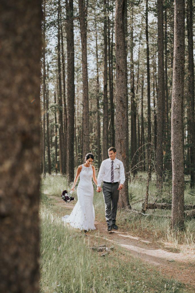 bride and groom laugh walking in elkwater woods