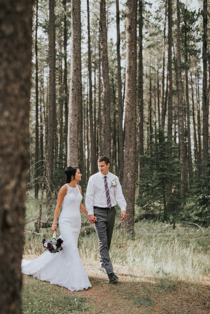 bride and groom hold hands walking in trees cypress hills