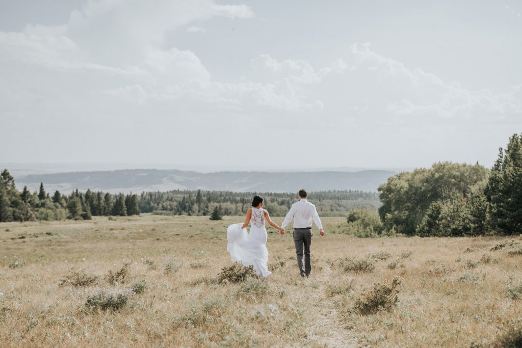 bride and groom hold hands running into field