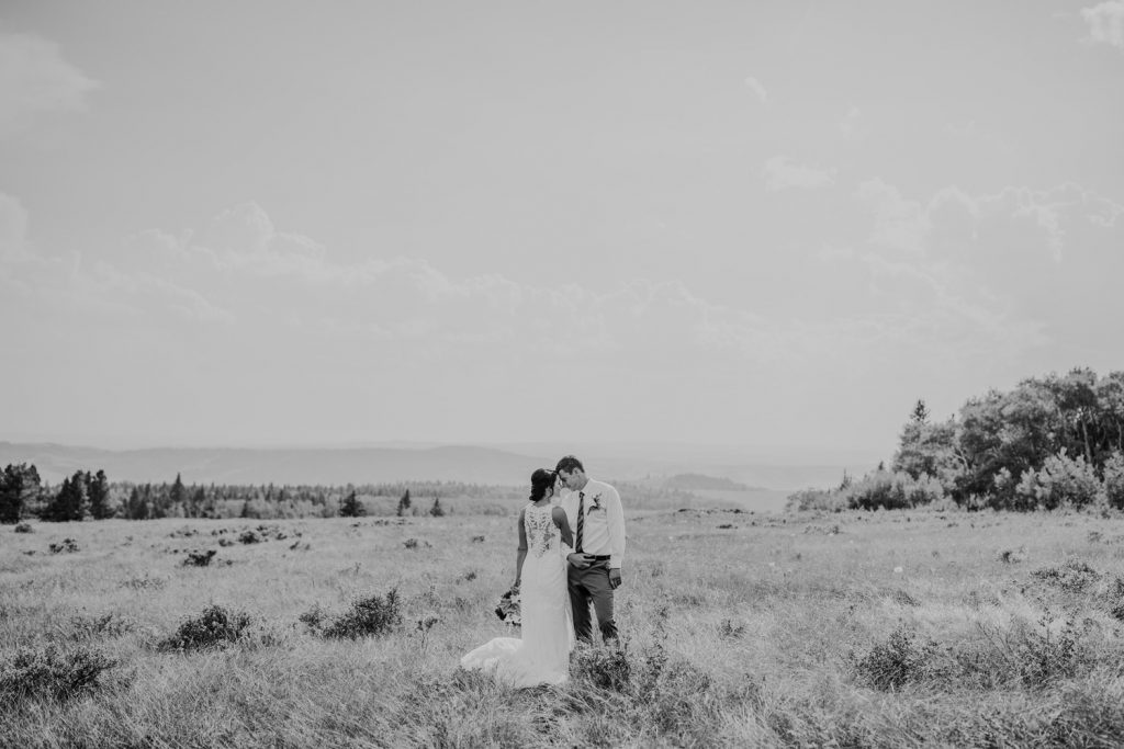 wedding couple standing close in field mountain view