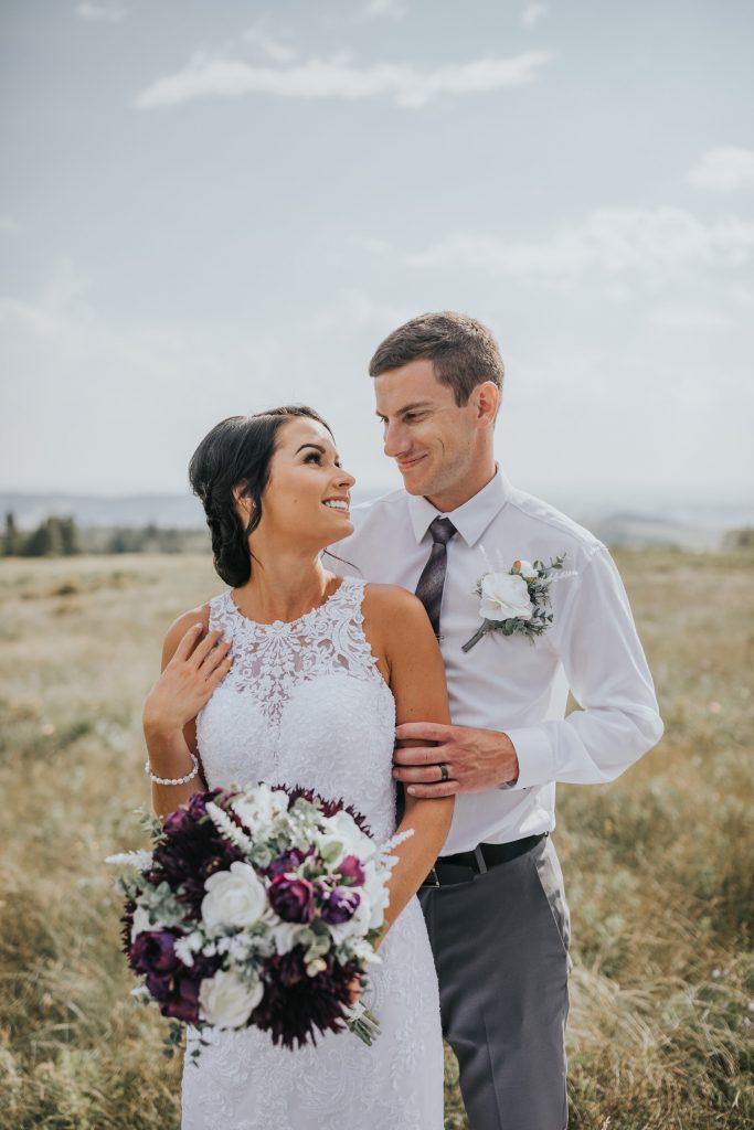 groom holds bride from behind wedding photo field