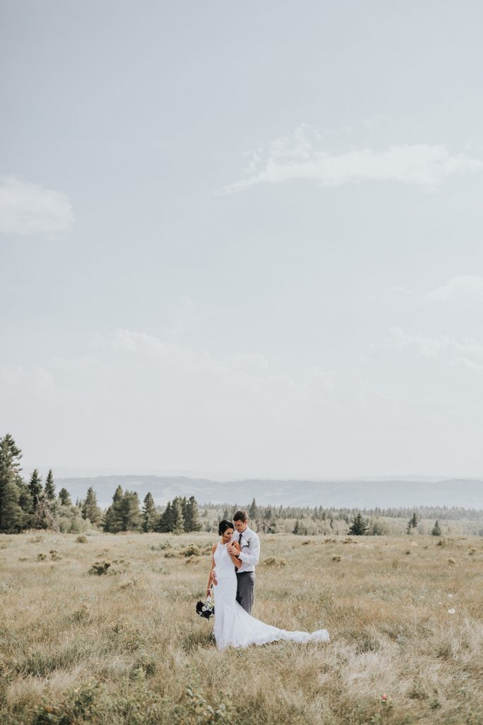 bride and groom standing in field with view