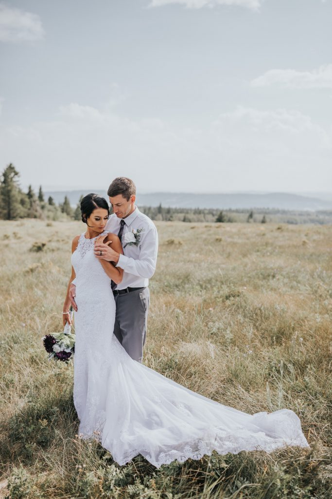 groom holds bride from behind