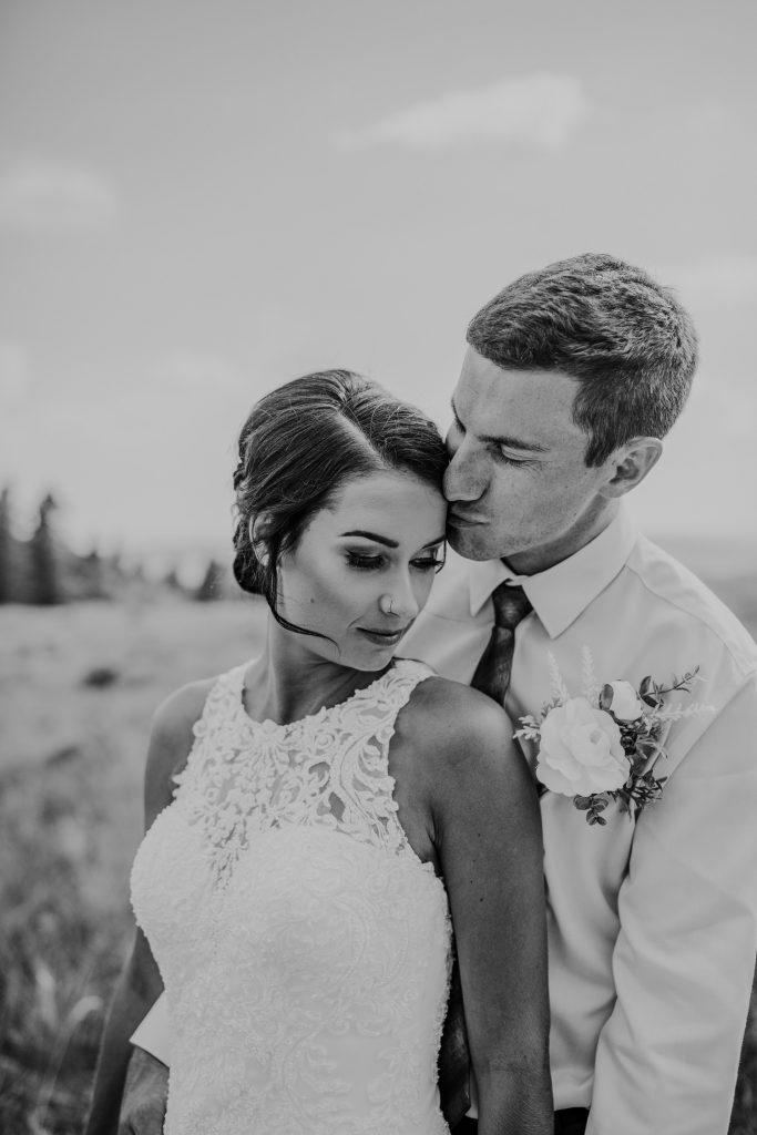 grooms kisses bride on head intimate wedding photo