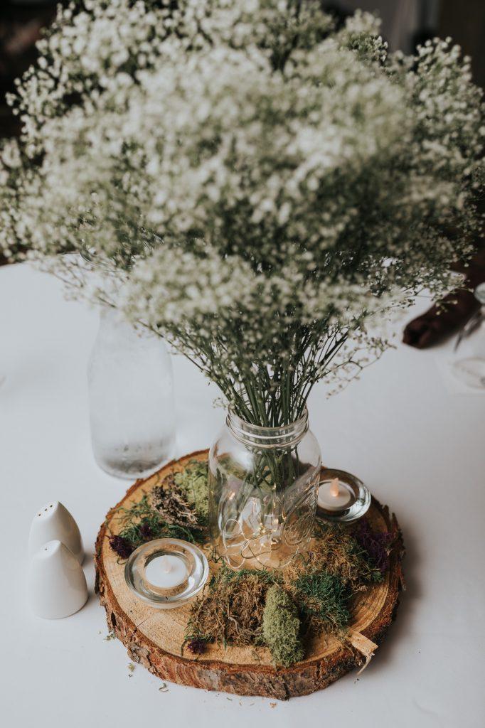 wedding reception centrepiece  greenery wood slab moss mason jar