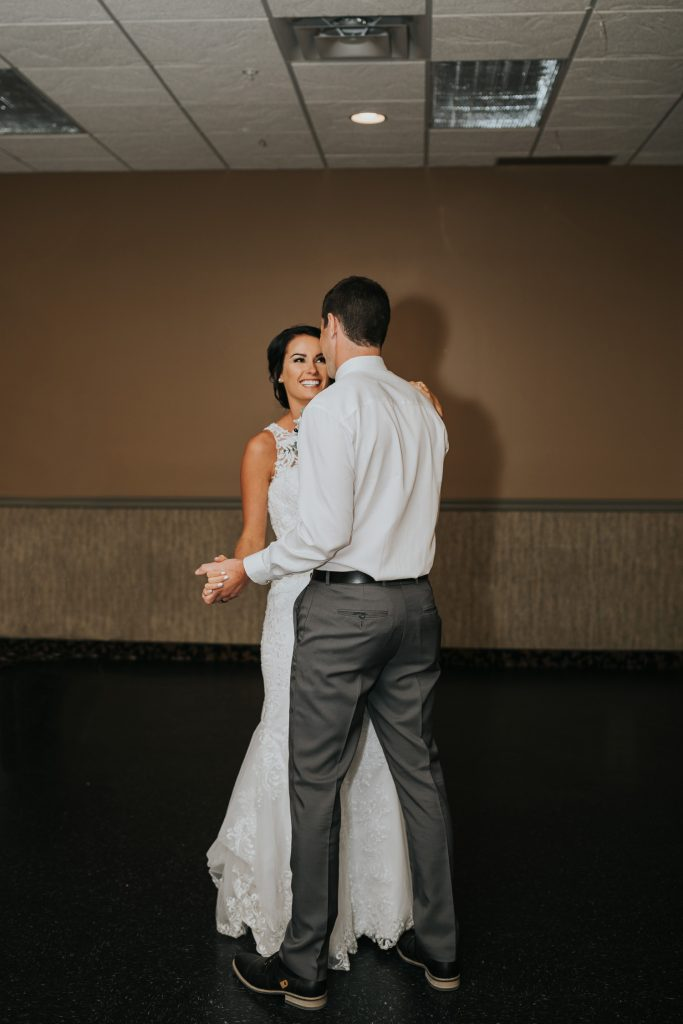 bride smiling at groom during first dance wedding reception