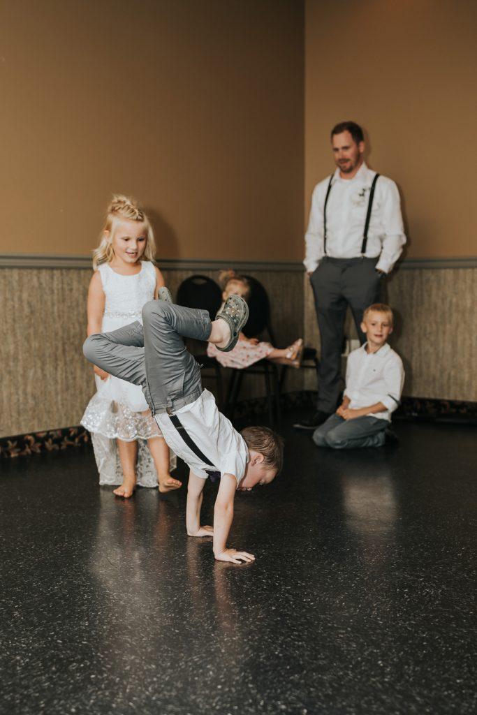 ring bearer little boy doing a handstand at wedding reception