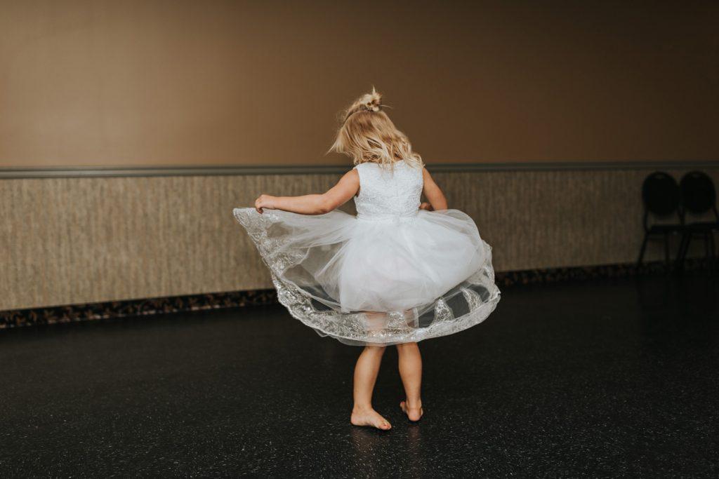 flower girl twirling her dress on dance floor wedding
