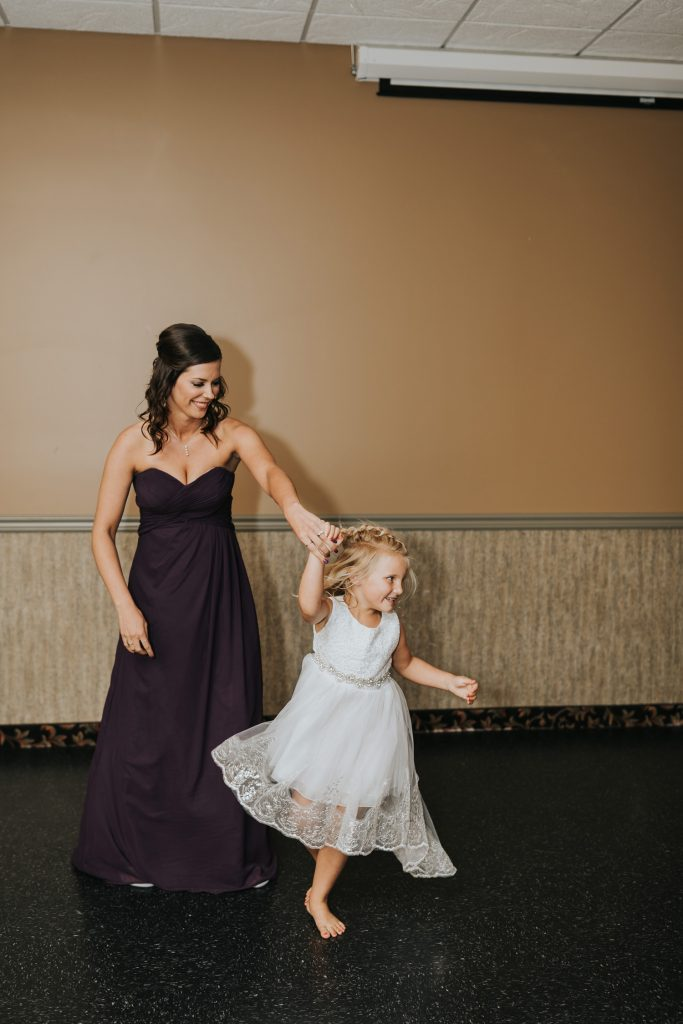 bridesmaid dancing with flower girl twirling