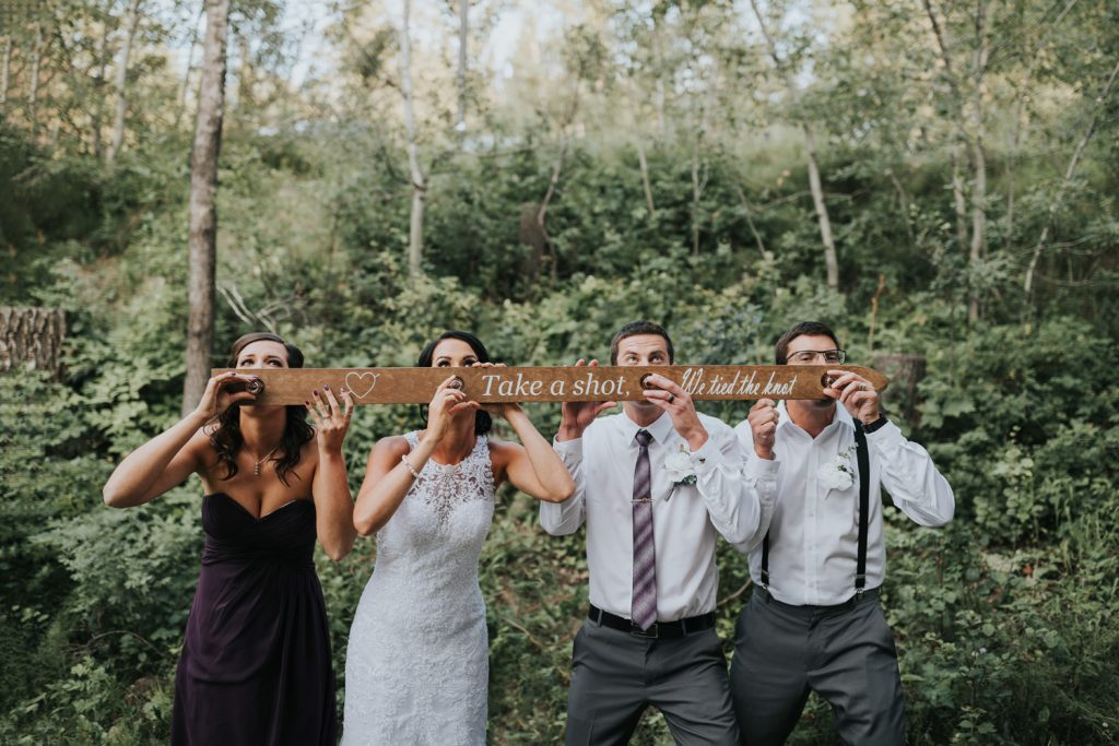 wedding party taking a shot from a shotski shot ski that reads take a shot we tied the knot