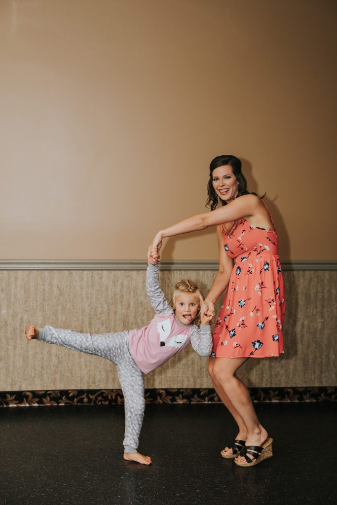 woman dancing with little girl making a funny pose