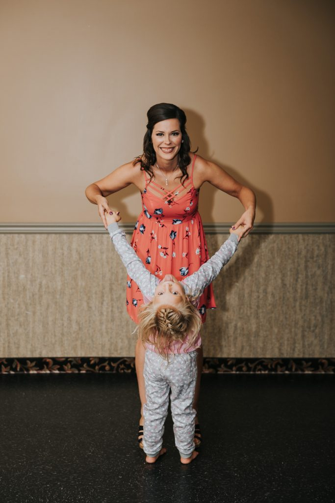 woman holding little girl as she makes a silly face upside down