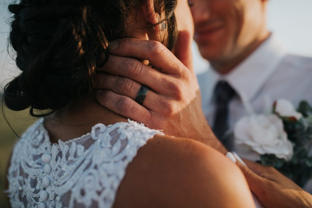 closeup of groom's ring with his hands caressing bride's face