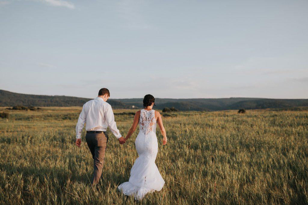 bride and groom walking away holding hands near Elkwater