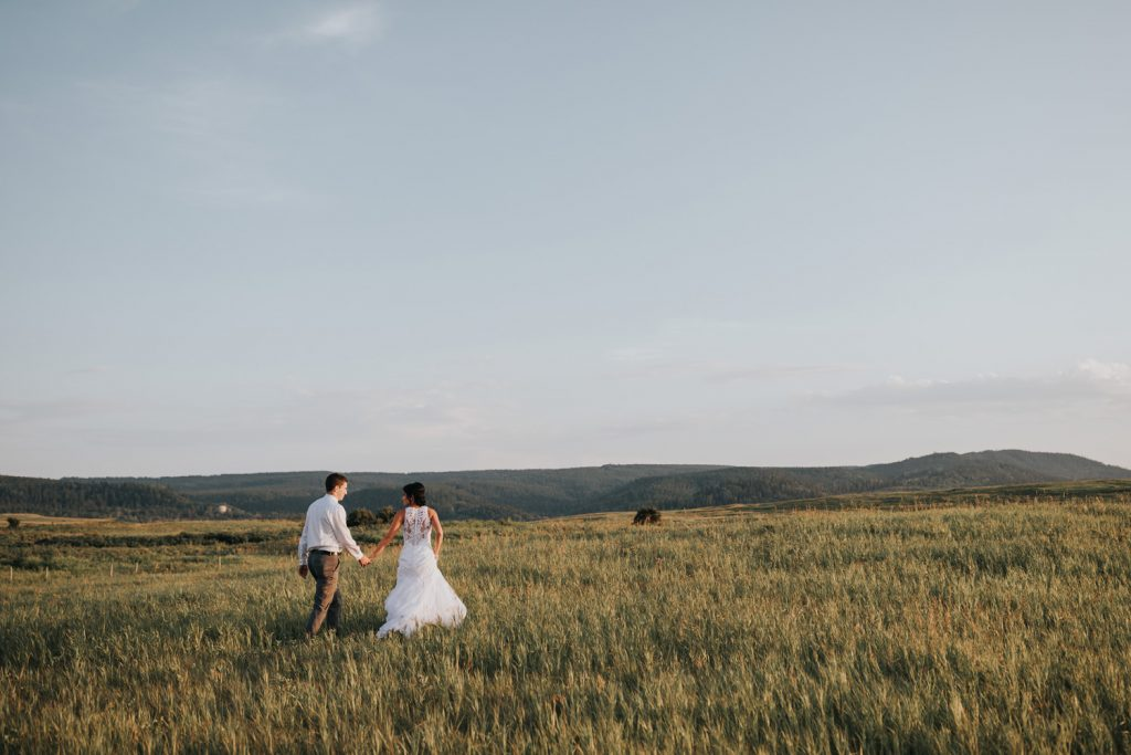 bride and groom run off in a field holding hands at sunset