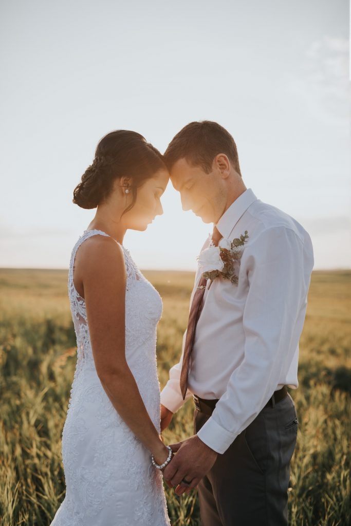 intimate bride and groom portrait holding hands foreheads touching with sunset behind them