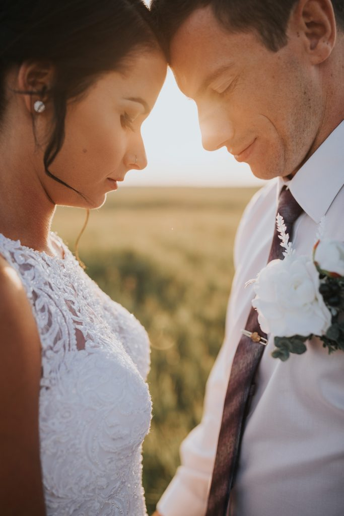 closeup of bride and groom with foreheads touching and eyes closed sunflare